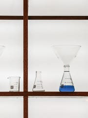 Beakers are displayed behind the bar as finishing touches are put on  Broken Beaker Distillery, 643 Massachusetts Ave., before the grand opening later in the week, Tuesday February 23rd, 2016.