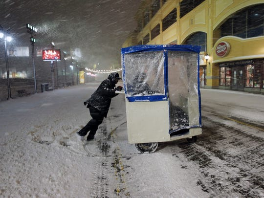 A man maneuvers his push cart with passengers during a snowstorm early Saturday on the Atlantic City Boardwalk. Most of the state was facing a blizzard warning from Friday evening until Sunday that called for up to 24 inches of snow, with the deepest accumulations in the central part of the state.
