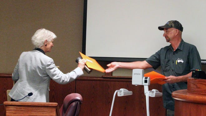Dale Ball, right, hands Redding City Councilwoman Francie Sullivan a recall notice during a recent council meeting.