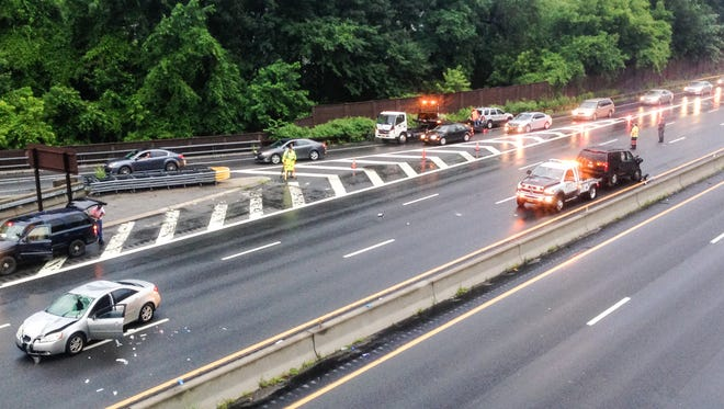 A flatbed prepares to tow a damaged vehicle from the scene of a fatal accident on the northbound Sprain Brook Parkway, July 1, 2015. Another damaged car remains on the parkway.