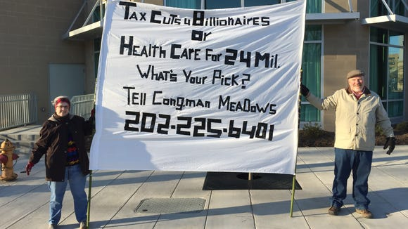 Affordable Care Act supporters Katie Winchell, left, and former City Councilman Chris Pelly hold a banner at the corner of Charlotte and College streets downtown Thursday morning. It refers to the number of people projected to lose health insurance under a proposed replacement for the law.