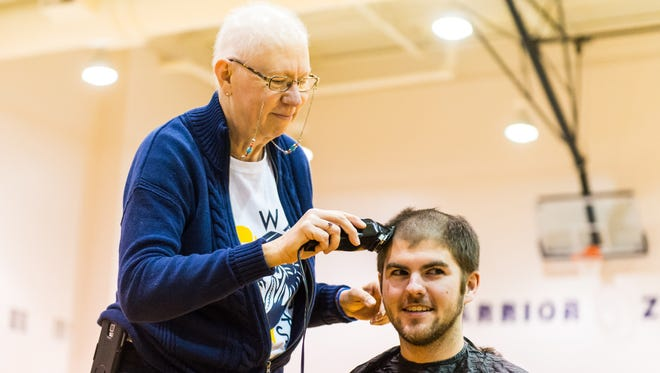 Pocomoke High girls basketball coach Gail Gladding shaves teacher Corey Zimmer's head during a pep rally as part of raising money for cancer research on Friday, December 18 in Pocomoke.