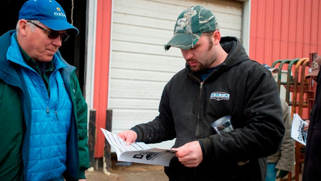 In this Friday, April 6, 2018 photo, Nate Elzinga, right, looks over the auction brochure during the dairy cow auction at his farm in Zeeland, Mich. Friday was the day of the auction where Elzinga and his partners sold the herd. Market forces and larger milking operations made it difficult for them to be profitable.
