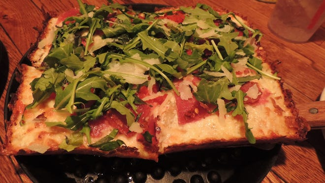A small (four slices, all corners) version of Brown Dog's Detroit-style 313 comes topped with ricotta, garlic, genoa salami, red Calabrian chili peppers, sweet piquante peppers, fresh basil, and arugula.