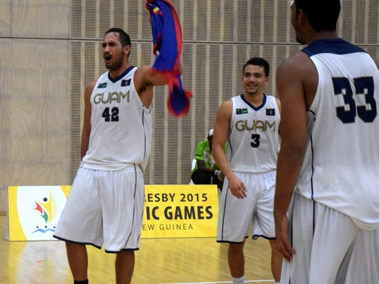 Team Guam's Tai Wesley waves the Guam flag after making 3-point shot to lift Guam over Fiji in men's basketball July 8 at the Taurama Aquatics Center and Indoor Sports Complex. Guam won in overtime 75-72 at the 2015 Pacific Games in Port Moresby, Papua New Guinea.