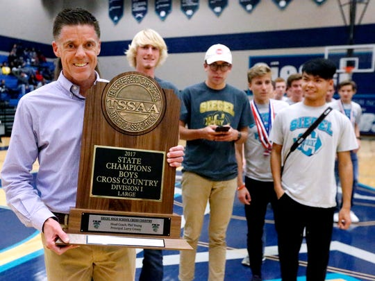 Siegel's head cross country coach Phil Young holds Siegel's Boys State Championship trophy after they were honored during the boys Siegel vs. Oakland game, on Tuesday, Dec. 5, 2017, at Siegel.