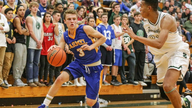 Carmel's #3 Cole Jenkins drives to the land past Zionsville's #32, Cassius Smits-Francisco, during the Zionsville VS Carmel boys basketball game at Zionsville High School, Tuesday November 24th, 2015.