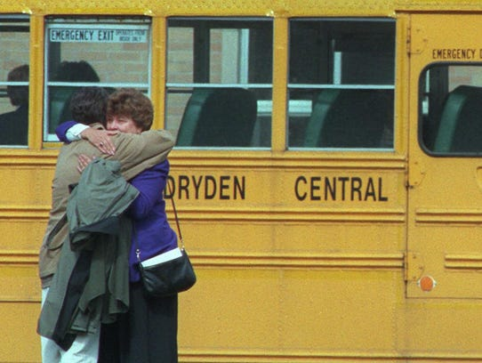 A couple comfort one another outside Dryden Central