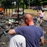 Timmy Roberts, 13, left, gets a hug from Josh Roberts while rummaging through the burnt remains of his home on Jefferson Township Road 350 near Warsaw. Only the eight lives were spared as the fire consumed all of the family's belongings as well as several pets.