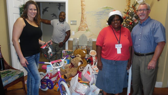 Hibiscus CEO Paul Sexton and staff were thrilled to receive many wonderful toys and gift cards at the shelter, delivered by Jennifer Brennan (left) from Hurricane Grill & Wings of Jensen Beach.
