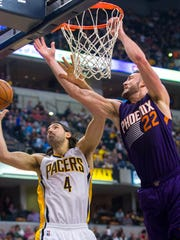 Indiana Pacer's Luis Scola (4) and Phoenix Sun's Miles Plumlee (22) battle for a rebound during the first half of an NBA basketball game, Saturday, Nov. 22, 2014, in Indianapolis.