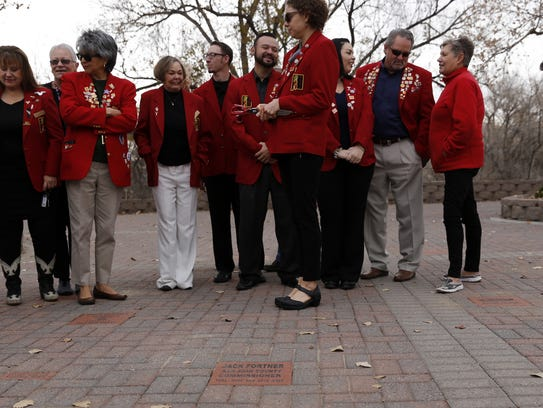 Members of the Farmington Chamber of Commerce Red Coats gather for a ribbon-cutting ceremony for a paver installation Wednesday in Berg Park in Farmington.