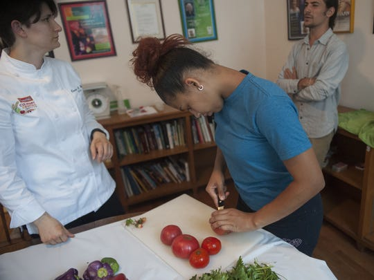 CFET's teenage farmers  Ashley Jackson, right, and Campbell's chef Carrie A. Welt cut some vegetables in preparations of a tomato gazpacho soup.