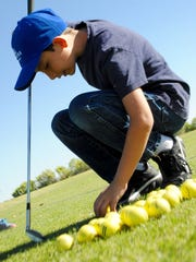 Alex Zander-Garcia sets up for a shot with a set of new golf clubs, courtesy the Clubs for Kids program.