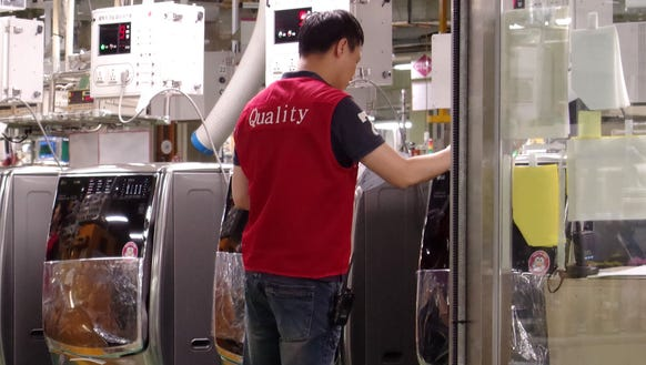 A quality control worker checks LG washing machines