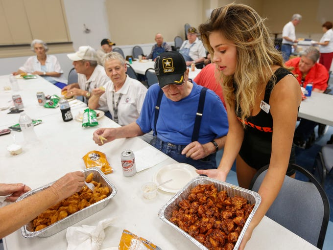 Mikayla Burch, a waitress at Hooters, serves wings