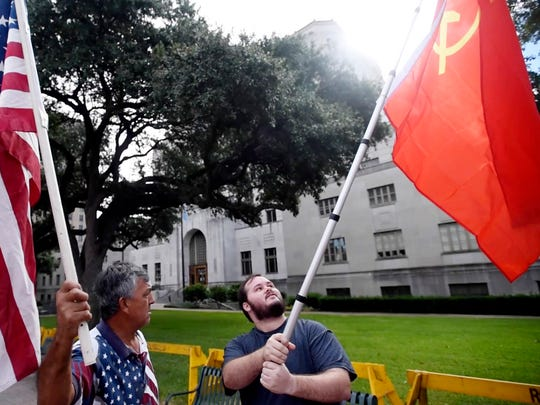 Chris Lyon, right, with a Soviet Union flag as Jesus Eguia, a monument supporter, stands with an American flag.