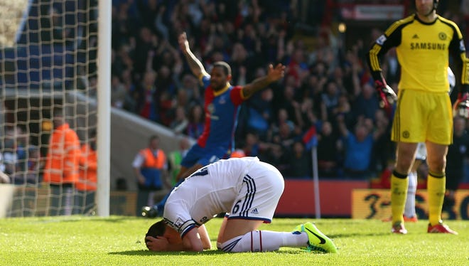 A dejected John Terry of Chelsea, left, reacts after opening the scoring with an own goal during the Barclays Premier League match against Crystal Palace.
