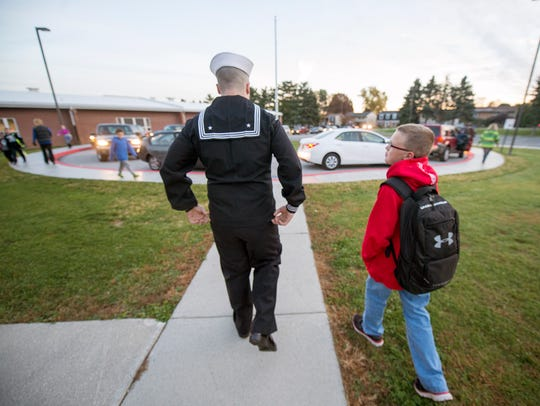 Chris Gray, left, and Austin Tyler, age 10, walk to