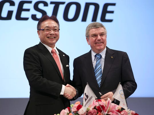 International Olympic Committee (IOC) President Thomas Bach, right, and Bridgestone Corp. CEO Masaaki Tsuya pose for photographers during a press conference in Tokyo, Friday, June 13, 2014. Japanese tire manufacturer Bridgestone signed an agreement on Friday to become a top-tier sponsor of the IOC in a 10-year deal that will cover the 2020 Tokyo Games. Bridgestone officials declined to reveal financial terms of the deal but the Asahi Shimbun newspaper reported that Bridgestone will pay $344 million to become a worldwide sponsor under the IOC's global commercial program, known as TOP. (AP Photo/Koji Sasahara)