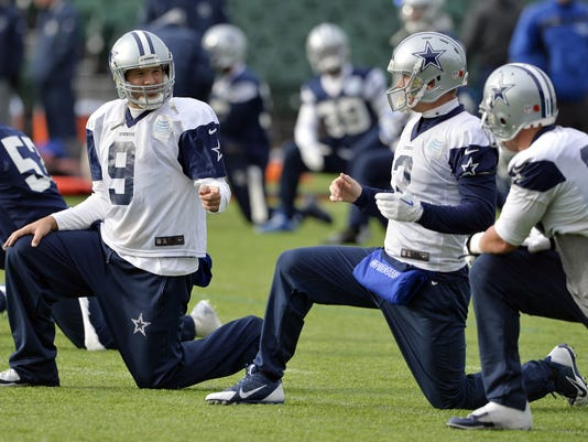 Dallas Cowboys quarterback Tony Romo, left, talks to teammate Brandon Weeden during a practice session in London, Thursday Nov. 6, 2014. The Dallas Cowboys will play the Jacksonville Jaguars in an NFL football game at Wembley Stadium on Sunday Nov. 9. (AP Photo/NFL UK, Sean Ryan)