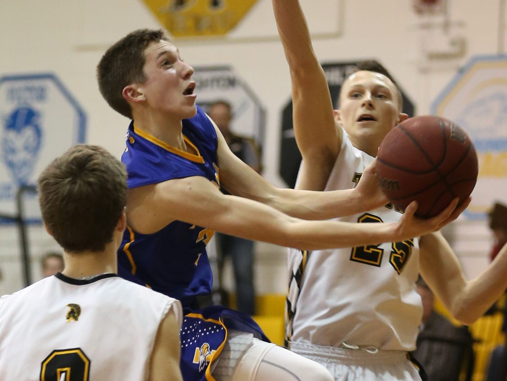 Irondequoit's Zach Stenglein, center, drives in between the defense of Athena's Adam Edinger, left, and Trevor Layne during their game Monday, Dec. 14, 2015 at Greece.