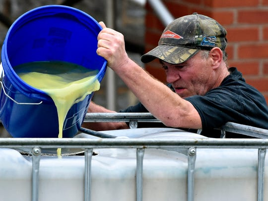 George Fisher, of Servpro, dumps a pail of fluid into