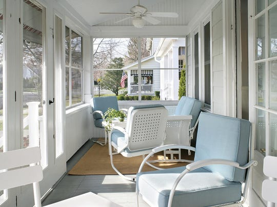 The screened-in porch on this mid-century beach house was updated while remaining in sync with the rest of the neighborhood. Raising the ceiling gave the space a more open feeling and made room for ceiling fans with light boxes to illuminate balmy summer evenings.