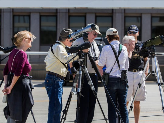 Birders set up spotting scopes to see group of Peregrine falcons from atop a parking garage in Downtown Wilmington on Thursday afternoon.