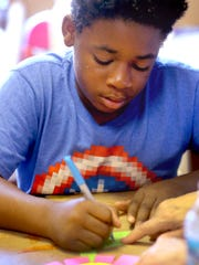 Bobby Turner, 11, writes what comforts him when he is grieving on the leaves of a flower as part of an art project at Camp Forget-Me-Not, on Thursday, June 23, 2016.r.