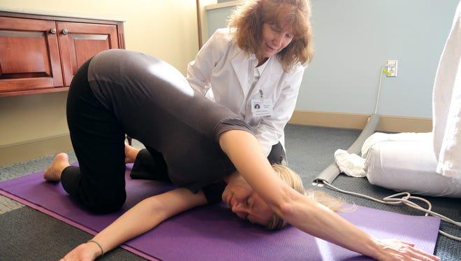 Yoga therapist Veronica Zador guides Susan Schreier during  a yoga session.
