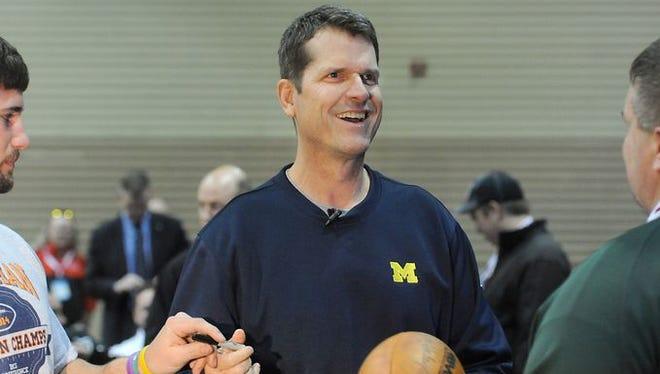 Michigan football coach Jim Harbaugh smiles at the Michigan High School Football Coaches clinic Friday, Jan. 16, 2015, in Lansing.
