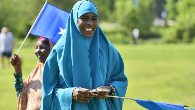Ubah Sheikhadan, right, and Khadija Hussein carry Somali flags during Somali Independence Day events in St. Cloud in June.