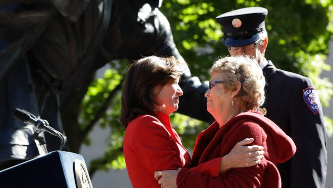 Lt. Gov. Kathy Hochul, left, embraces Loretta Miller at a ceremony at the New York State Fallen Firefighters Memorial on on Tuesday in Albany. Loretta Miller's son, Barry Miller, died in a crash in Riga last year.