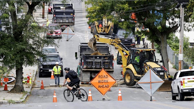 FILE - A bicyclist takes a turn at a road block as utility contractors dig up the road above natural gas lines along Brookfield Street in Lawrence, Mass., Thursday, Sept. 20, 2018. Nearly 9,000 homes and businesses may be without gas for weeks as investigators continue to probe what set off the explosions last Thursday in the Merrimack Valley area serviced by Columbia Gas of Massachusetts.