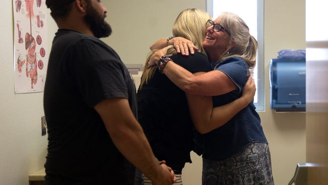 From left, Myron Voorhis watches as his wife Nicole Voorhis hugs Carol Ewing, a certified nurse midwife, Monday, July 11, 2017 at San Juan Health Partners Family Medicine Clinic in Aztec.