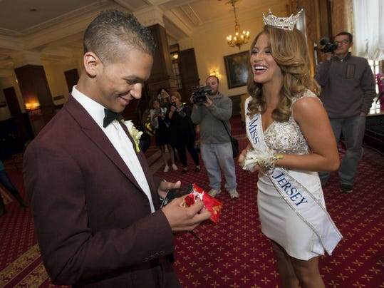 Marcus Josey, left, is all smiles as he opens up a gift from Miss New Jersey Lindsey Giannini in the lobby of the Yorktowne Hotel on Saturday. Josey, who is battling leukemia, asked Giannini to his homecoming at Northeastern, and she accepted.