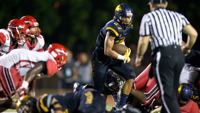 Naples' Chez Mellusi carries the ball in the fourth quarter of action at Naples High School Friday, September 23, 2016 in Naples. Naples won 60-42.