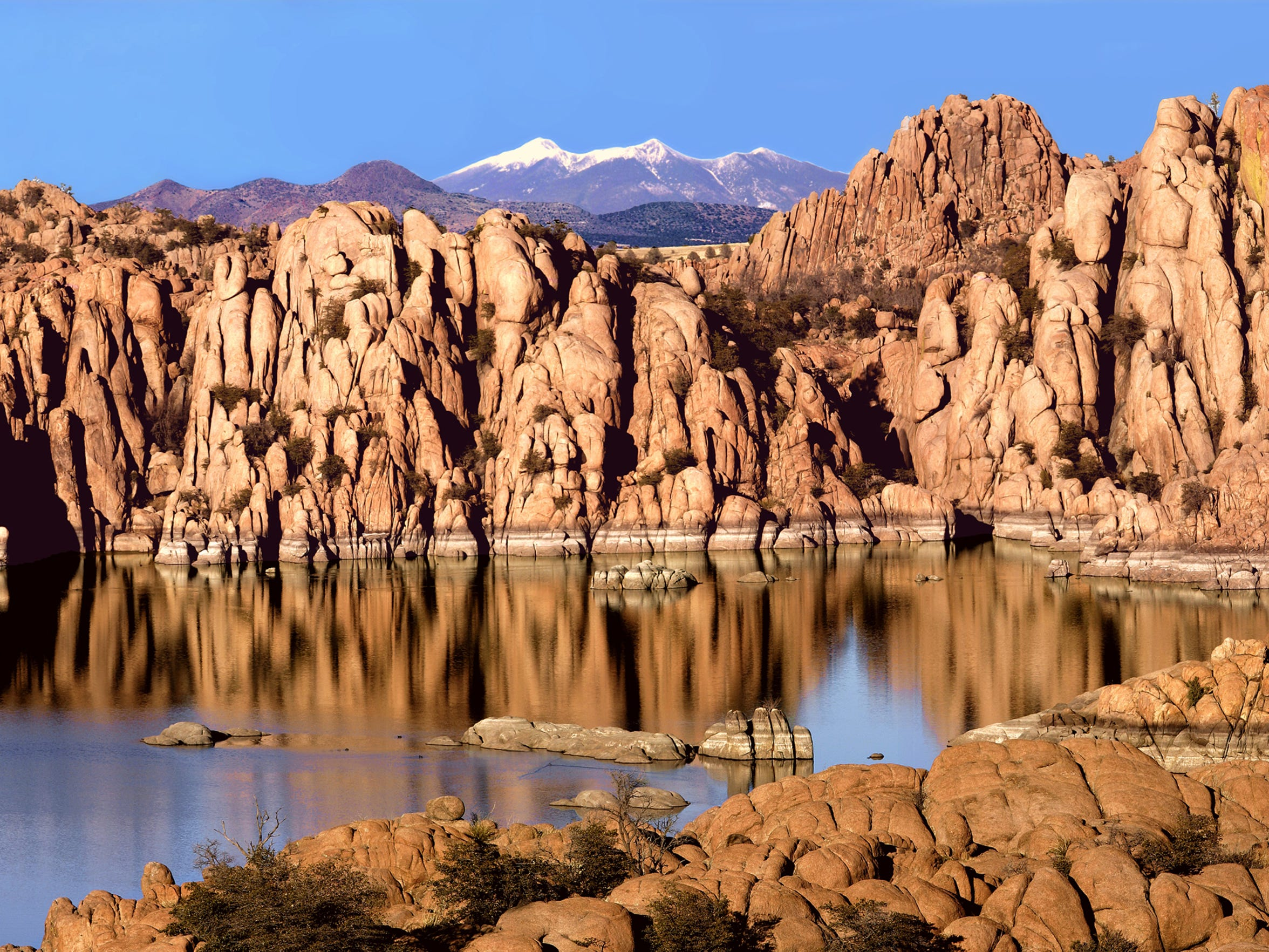 The intricate rocks of Watson Lake near Prescott frame the San Francisco Peaks in the distance. Watson Lake is one of several lakes in the Prescott area.