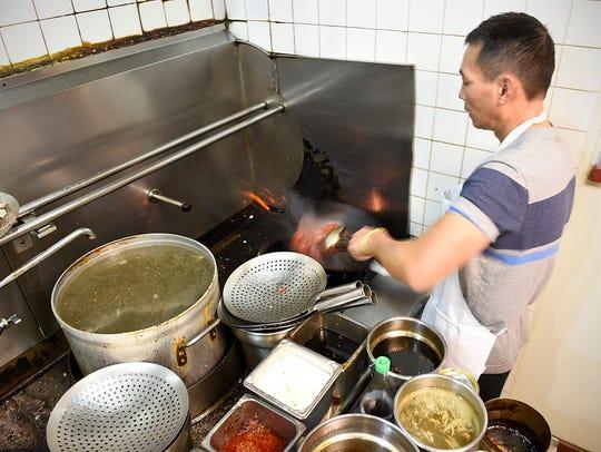 Khan Nguyen makes sesame chicken at D&K Express in
