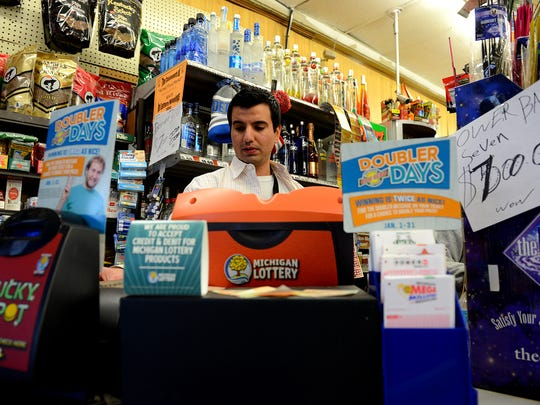 Randy Thomas, manager at Sunset Food Mart, operates the lottery machine to get a customer their tickets Friday, January 8, 2015, in Lansing. The Powerball jackpot is at $800 million.