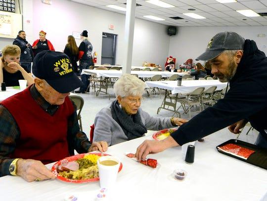 Volunteer John Myers of Dover serves dinner to World