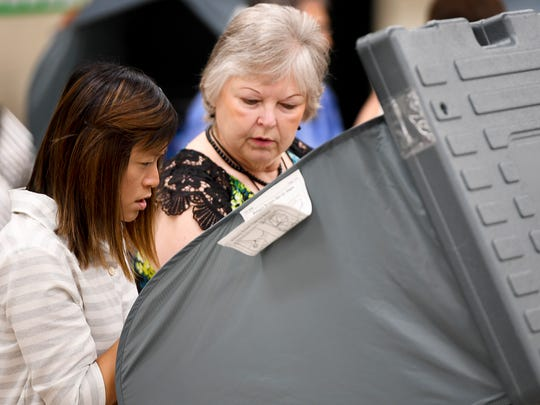 First time voter Yuk Jung Shahan is helped by Nelda Doss on how to use the voting machine, Friday, July 20. Early voting continues through July 28 at the Madison County Agricultural Complex Auditorium.