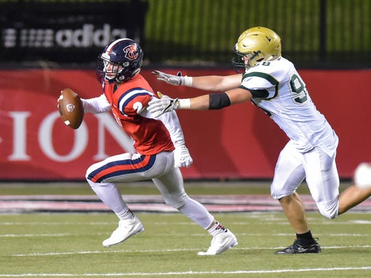 Teurlings quarterback Hayden Cantrelle escapes a tackle by Acadianas Blaise Davis at the Kiwanis Football Jamboree. August 26, 2016