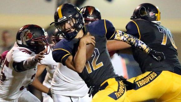 Eastwood quarterback Mark Torrez, 12, rushes into the