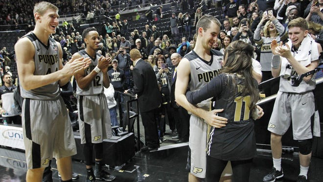 With his Purdue basketball teammates looking on, Stephen Toyra and  his girlfriend, Taylor Vauters, embrace after Toyra proposed to her after the Boilermakers 68-55 victory over Vanderbilt Tuesday, December 22, 2015, at Mackey Arena.