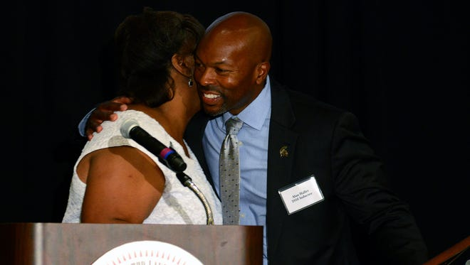 Former NFL and MSU football player Alan Haller gets a hug as he's given a special award from the MSU Black Alumni Association during the Lansing Sports Hall of Fame banquet Thursday, July 28, 2016 at the Lansing Center. Haller was a four year letter winner in football at MSU and went on to play professionally for the Steelers, Brown and Panthers. He graduated from Sexton where he played football and was a member of the 1986 and 1987 state championship track teams.