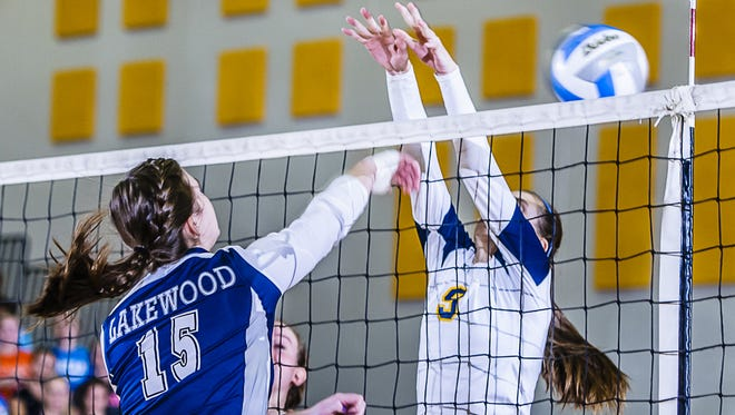 Vanessa Reynhout (left) of Lakewood hits past Elizabeth Anast of DeWitt during their CAAC Cup Championship game Thursday October 25, 2012 in DeWitt.