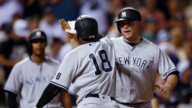 New York Yankees' Didi Gregorius, left, is congratulated by Brian McCann as Gregorius heads back to the dugout after hitting a three-run home run off Colorado Rockies relief pitcher Gonzalez Germen during the sixth inning of a baseball game Tuesday, June 14, 2016, in Denver.