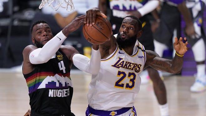 Denver Nuggets forward Paul Millsap (4) has his shot blocked by Los Angeles Lakers' LeBron James (23) on Tuesday in Lake Buena Vista, Fla.